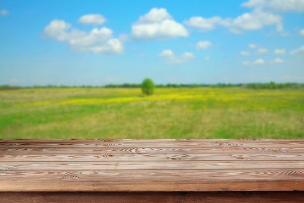 Table en bois vide dans le contexte du champ fleuri de printemps. un espace vide pour votre objet.