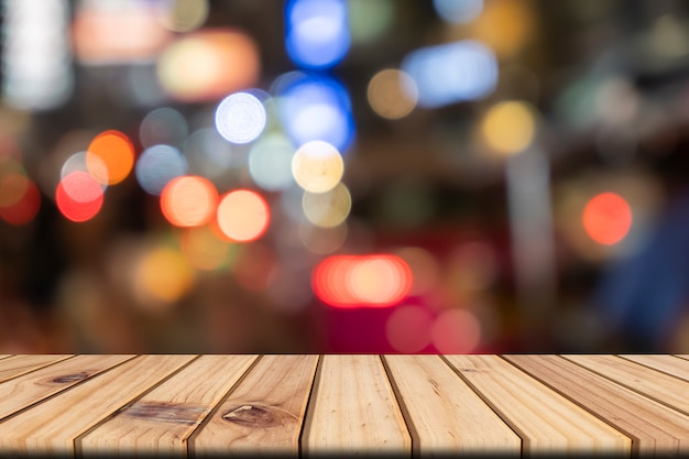 Table en bois vide en face avant abstrait bokeh floue fond coloré