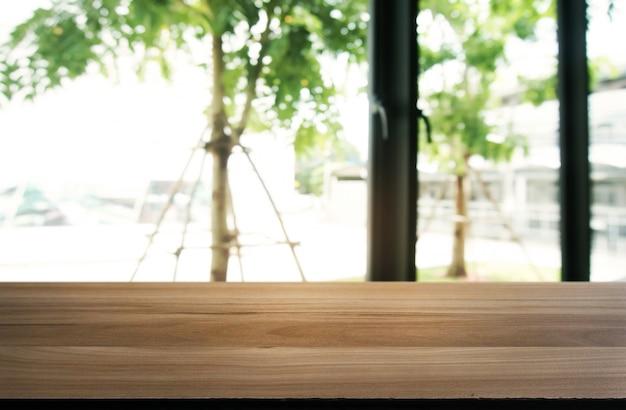 Table en bois vide en face de fond abstrait et flou du restaurant. peut être utilisé pour l'affichage ou le montage de vos produits. enregistrez l'affichage du compteur.
