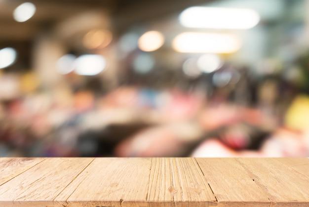 Table en bois vide en face d'un fond de verre abstrait et abstrait. peut être utilisé pour l'affichage mock up of product