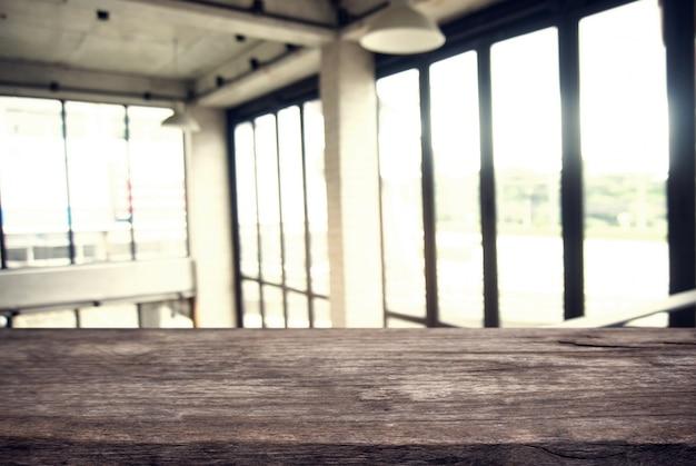Table en bois vide en face d'un fond de verre abstrait et abstrait. peut être utilisé pour l'affichage ou le montage de vos produits.moteur pour l'affichage du produit