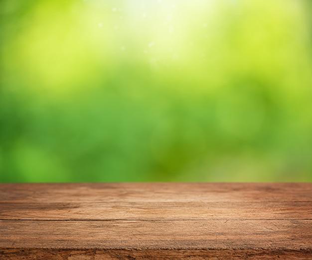 Table en bois vide avec fond de nature verte abstraite ensoleillée défocalisé.