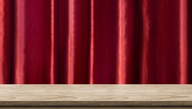 Table en bois vide et fond de rideau de luxe rouge vif floue.