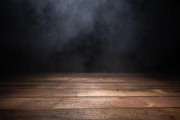 Table en bois vide avec de la fumée flottant sur fond sombre