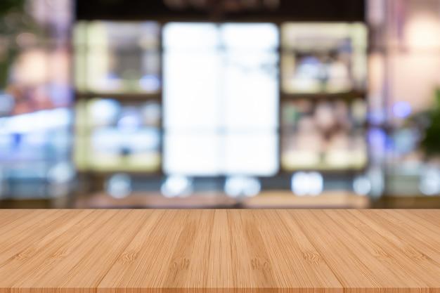 Table en bois vide de perspective sur le dessus sur fond flou.