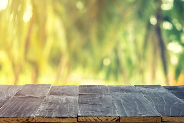 Table en bois vide pour le montage de l'affichage du produit et flou de cocotier sur la plage en été.