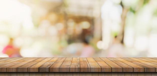 Table en bois vide et table lumineuse floue dans un café et un café avec un arrière-plan flou. modèle d'affichage du produit.