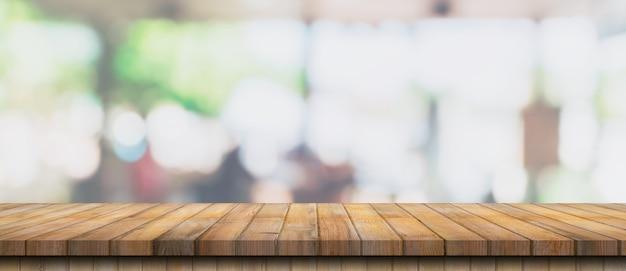 Table en bois vide et table lumineuse floue dans un café et un café