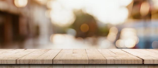 Table en bois vide et table lumineuse floue dans un centre commercial avec fond de bokeh. modèle d'affichage de produit.