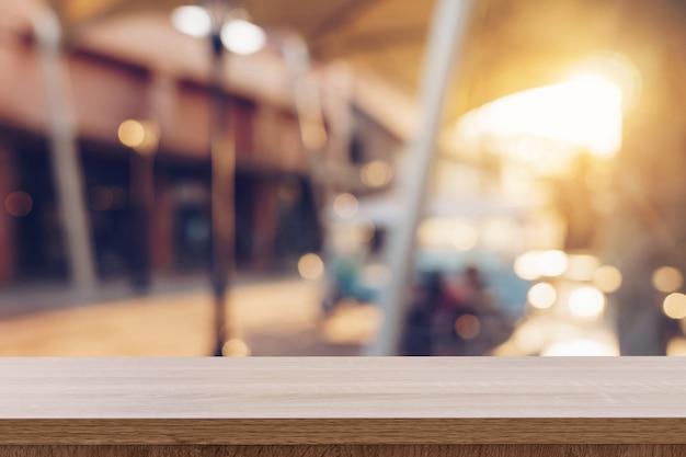 Table en bois vide et ton vintage flou défocalisé des gens de la foule au festival de la rue et au centre commercial.