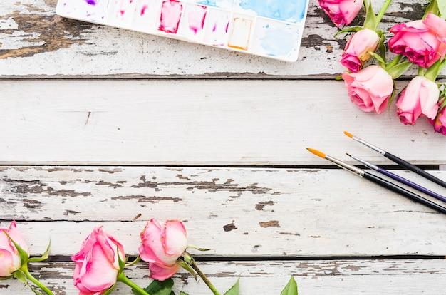 Table en bois vue de dessus avec des fleurs et des pinceaux