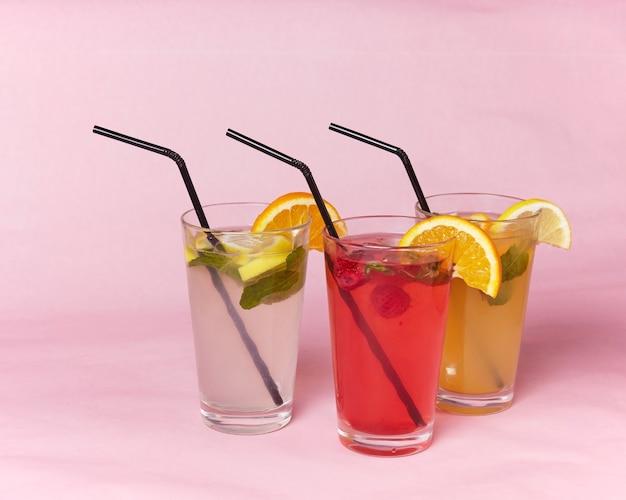 Sur la table, des boissons gazeuses, divers cocktails, un verre avec une paille et une tranche de citron, une surface floue