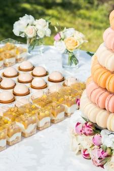 Table avec des bonbons décorés de fleurs et gâteau macaron