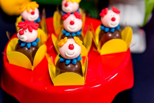 Table avec des bonbons et des muffins décorés de glaçage royal lors d'une fête d'enfants.