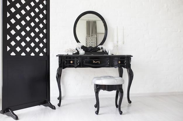 Table de boudoir noire dans une pièce lumineuse avec un mur de briques blanches.