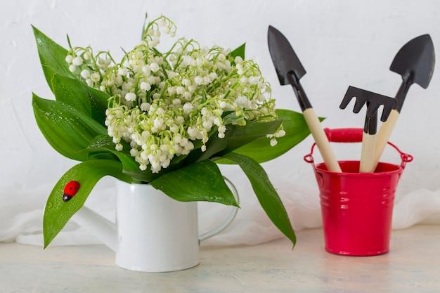 Sur la table un bouquet de muguets est placé dans un arrosoir et un seau