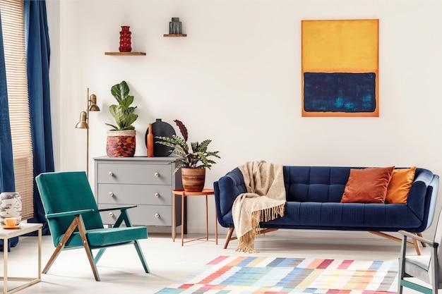 Table de bout orange avec plante fraîche debout à côté d'un canapé bleu marine avec couverture et oreillers à l'intérieur du salon blanc avec peinture, fauteuil vert, vases sur étagères et tapis coloré au sol