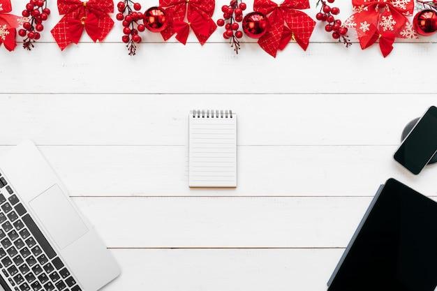 Table de bureau avec appareils, fournitures et décor de noël