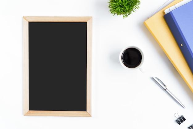 Table de bureau blanc et équipement pour travailler avec du café noir et un tableau blanc dans la vue de dessus et le concept de ray plat.