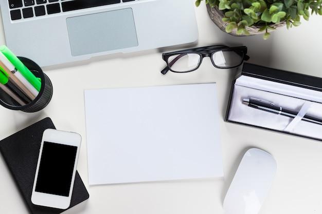 Table de bureau blanche avec beaucoup de choses dessus, vue de dessus