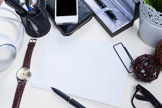 Table de bureau blanche avec beaucoup de choses dessus. vue de dessus