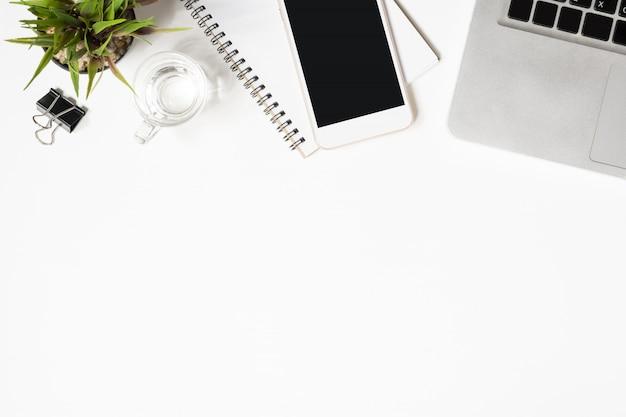 Table de bureau blanche avec beaucoup de choses dessus.