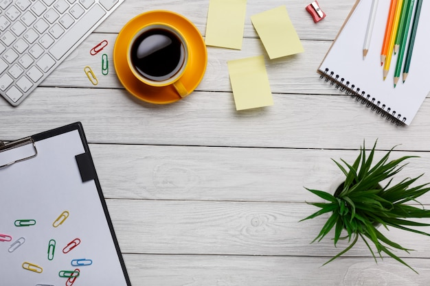 Table de bureau blanche avec bloc-notes vierge, ordinateur, fournitures et tasse à café.