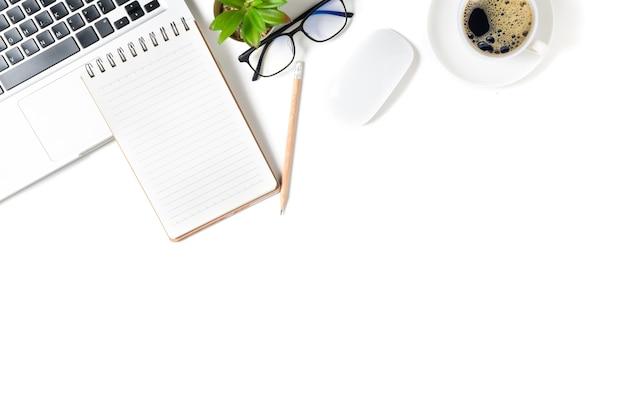 Table de bureau blanche, cahier vierge avec ordinateur portable et café chaud.