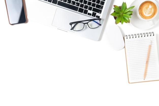 Table de bureau blanche, cahier vierge avec ordinateur portable et café.