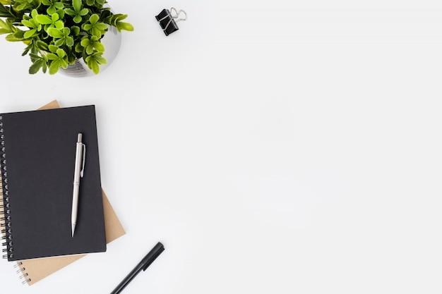 Table de bureau blanche avec cahiers et stylos.