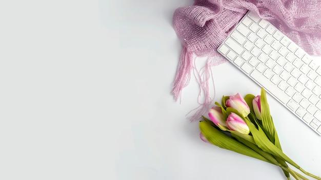 Table de bureau blanche avec clavier et fleur. vue de dessus avec espace de copie. plat poser.