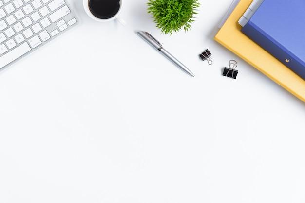 Table de bureau blanche et équipement pour travailler avec un café noir dans la vue de dessus et le concept de ray plat.