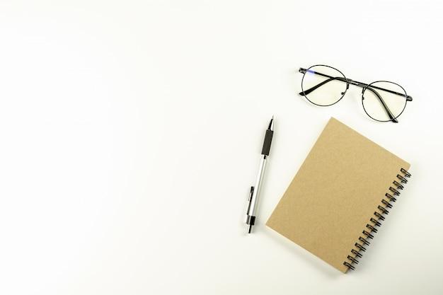 Table de bureau blanche avec des lunettes, un stylo et un cahier marron