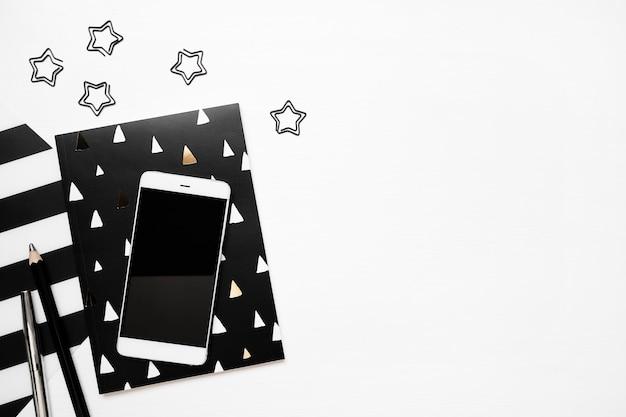 Table de bureau blanche moderne avec bloc-notes élégant, smartphone et autres clips