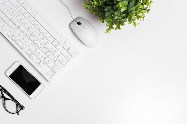 Table de bureau blanche moderne avec clavier et fournitures.