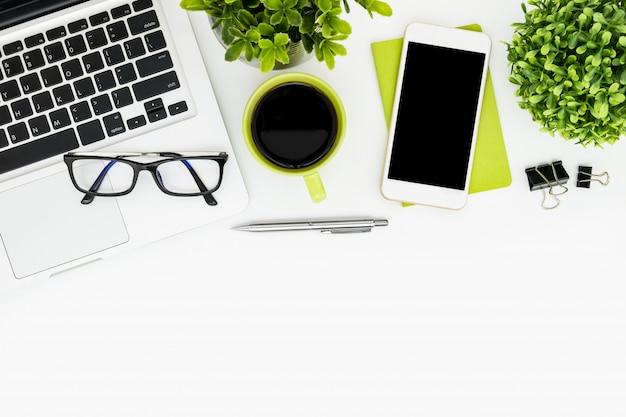 Table de bureau blanche avec ordinateur portable, café, fournitures et plantes.