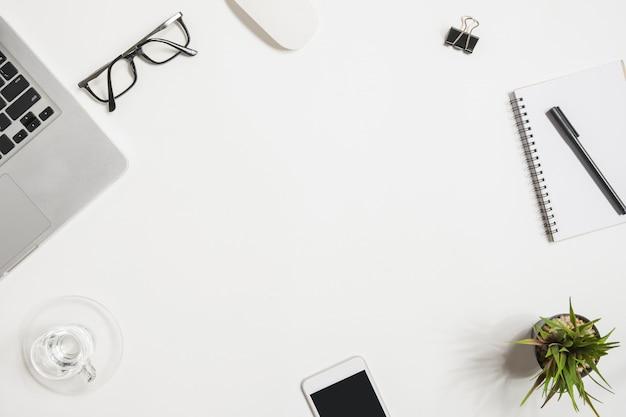 Table de bureau blanche avec ordinateur portable et fournitures. t