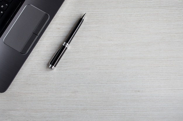 Table de bureau blanche avec ordinateur portable et stylo. arrière-plan de la vue de dessus avec fond. espace de travail sur la table. concept de travail et de bureau