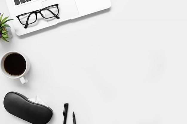 Table de bureau blanche avec ordinateur portable, tasse de café et fournitures.