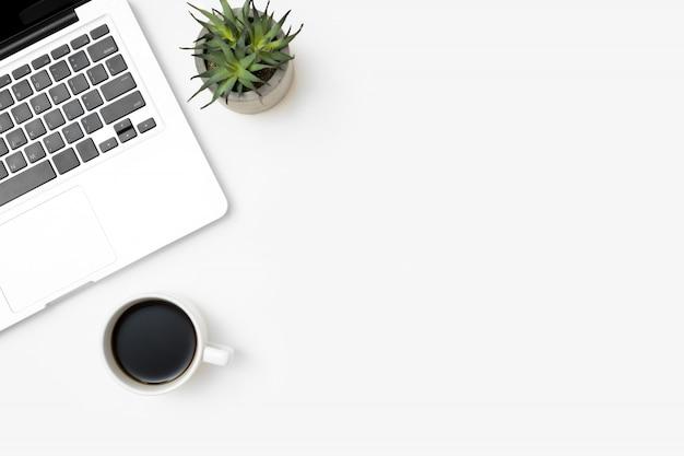 Table de bureau blanche avec ordinateur portable et tasse de café.