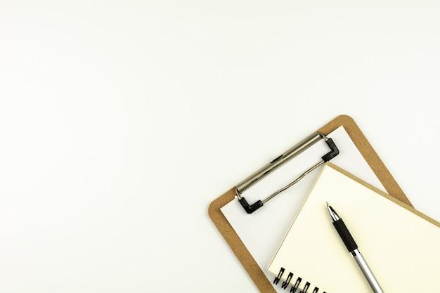 Table de bureau blanche avec un stylo sur un cahier vierge. - vue de dessus avec espace de copie.