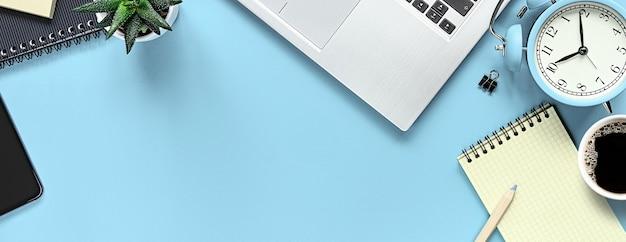 Table de bureau avec bloc-notes, ordinateur portable et réveil. vue d'en haut avec espace de copie. photo à plat du bureau de l'espace de travail.