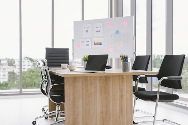 Table de bureau avec bloc-notes vierge et poste de travail pour ordinateur portable
