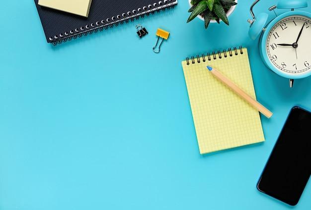 Table de bureau avec blocs-notes, smartphone, plante et réveil. vue d'en haut avec espace de copie. photo à plat du bureau de l'espace de travail.