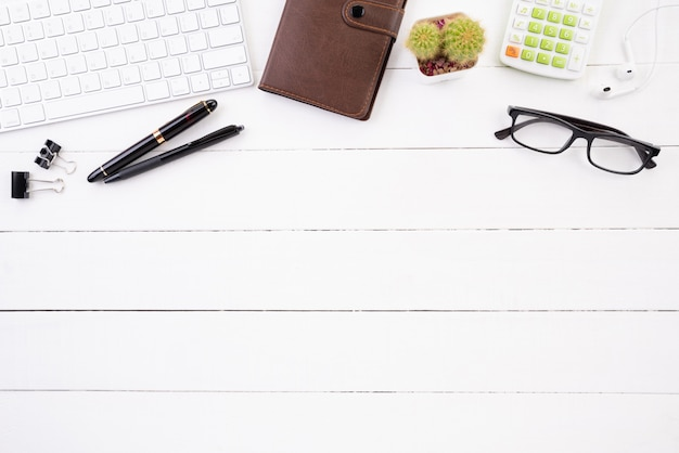 Table de bureau en bois blanc avec accessoires.