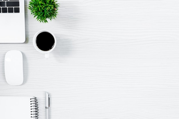 Table de bureau en bois blanc et équipement pour travailler avec un café noir dans la vue de dessus et le concept de ray plat.