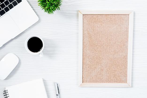 Table de bureau en bois blanc et équipement pour travailler avec le café et le tableau blanc dans la vue de dessus et le concept de ray plat.