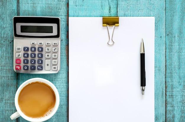 Table de bureau en bois bleu avec rame de papier, stylo, calculatrice et tasse de café.