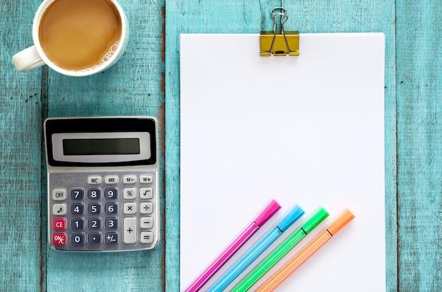 Table de bureau en bois bleu avec rame de papier, stylo de couleur, calculatrice et tasse de café.