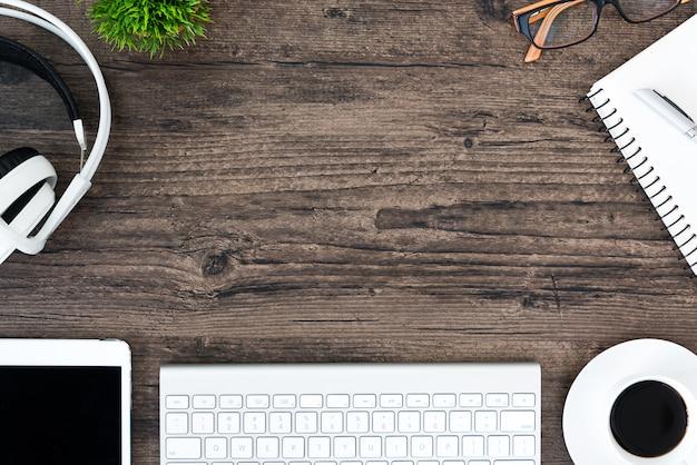 Table de bureau en bois brun et équipement pour travailler et écouter de la musique avec un casque blanc en vue de dessus et espace de copie.